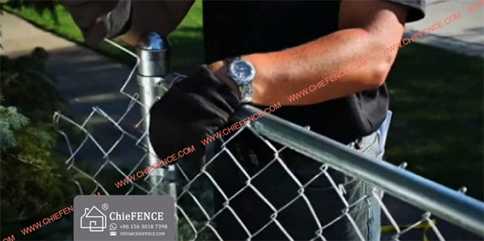Without releasing the fence puller, insert a tension bar in the mesh close enough so it can be fastened to the tension bands on the end post nearest the fence puller. To remove the excess mesh between the tension bars and end post, open a loop at the top and bottom, then twist and pull the strand free.